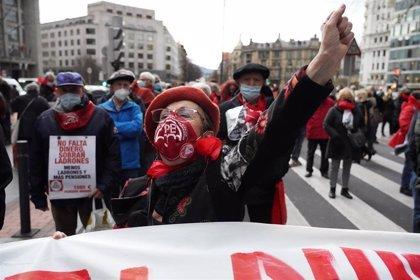 Manifestación de pensionistas por las pensiones, con una mujer en primer plano con el brazo levantado y boina roja.