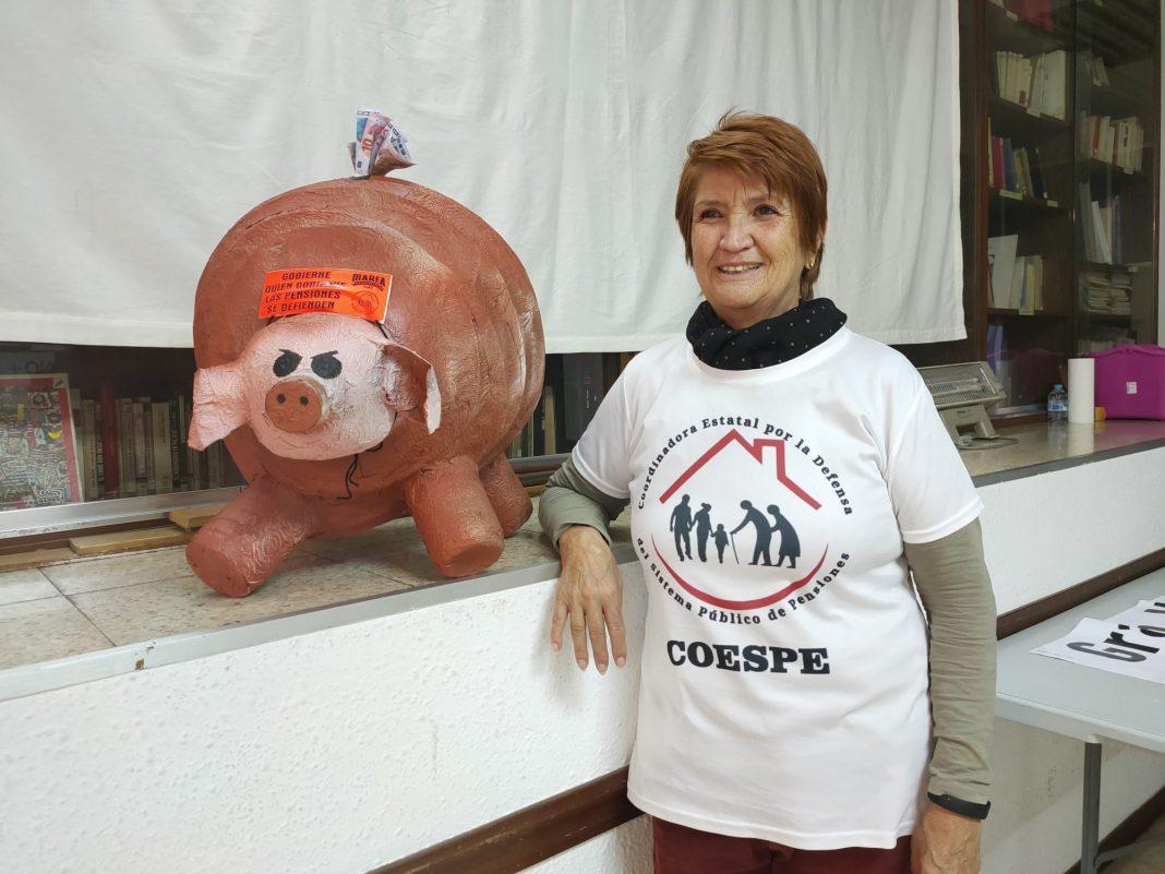 Mujer, de nombre Conchita Ribera, con una camiseta blanca con el logo de COESPE, coordinadora del movimiento pensionista, junto a una hucha gigante con forma de cerdo que emula la hucha de las pensiones.