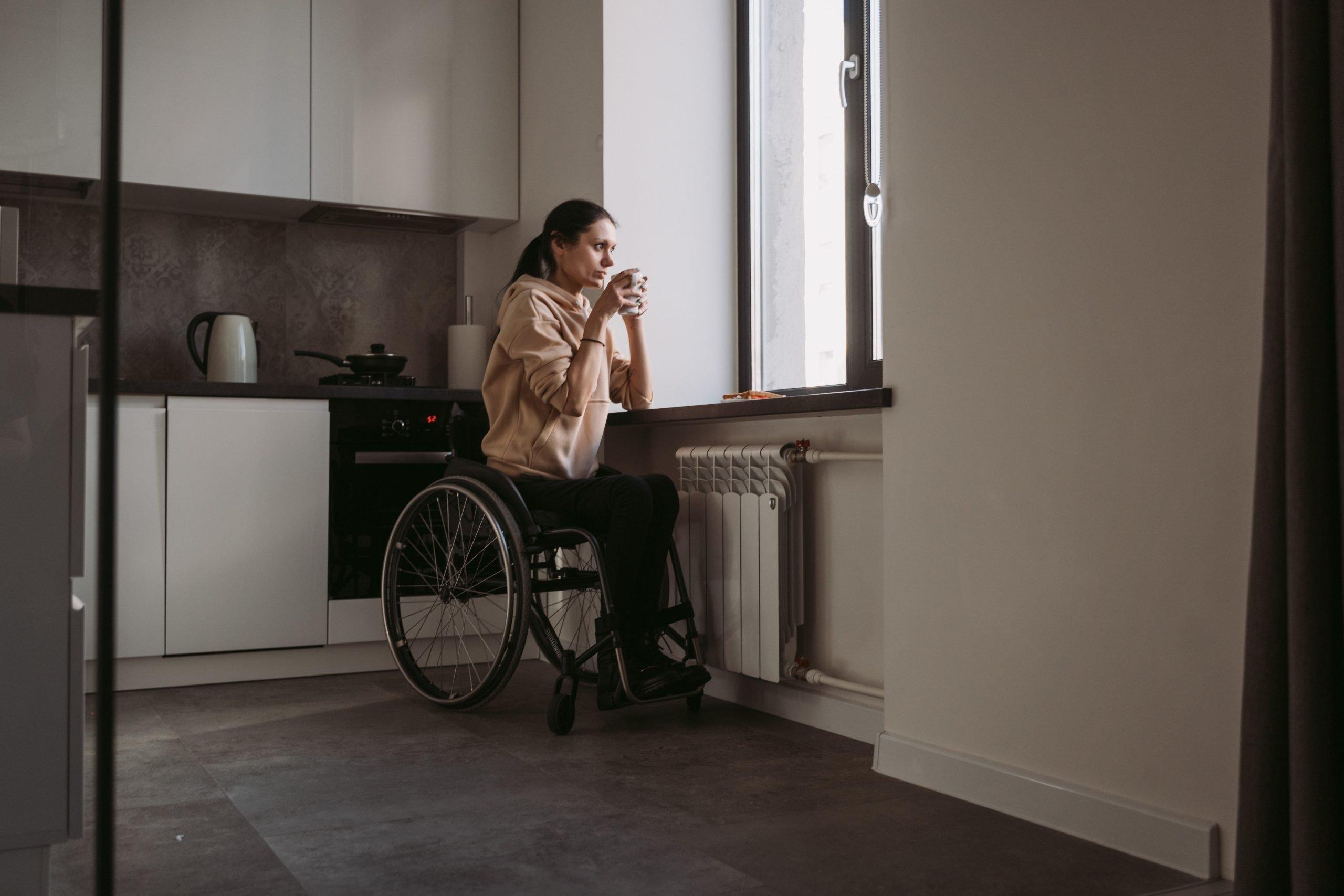 Mujer en silla de ruedas tomando café en su casa / © Mart production. Pexels